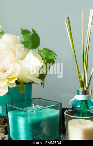 Reed diffuser with wooden sticks in turquoise glass bottle candles bouquet of flowers on table gray wall background. Aromatherapy home interior decor  - Stock Image