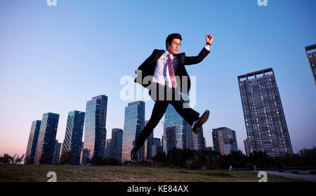 Businessman jumping against skyscrapers in city at sunset - Stock Image