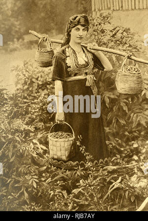 Young peasant woman in traditional dress with embroidered bodice, Bulgaria. She is carrying baskets of wild berries. - Stock Image