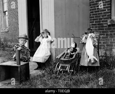 In an apparent set up comic photo, the children prepare to set off some dynamite for some good, clean fun, ca. 1900 - Stock Image