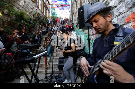 Amman, Jordan. 24th Apr, 2019. Yacoub Abu Ghosh (1st R), a Jordanian composer and performer, and Bal Qeis (2nd R), an Egyptian singer and oud player, perform at a free street concert near Shamasi stairs, downtown Amman, Jordan, on April 24, 2019. The 8th Amman Jazz Festival is held here between April 19 and 25. Credit: Mohammad Abu Ghosh/Xinhua/Alamy Live News - Stock Image