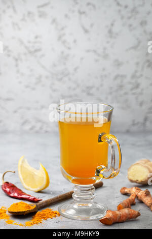 morning detox drink turmeric in the glass on a gray concrete background. copy space - Stock Image