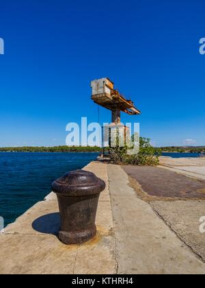 Rusty bollard and abandoned sea-derrick crane in ex-JNA Yugoslav Army port Minerska bay before Sibenik city in Croatia - Stock Image