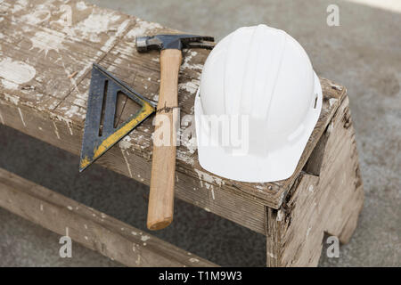 Hard-hat, hammer and ruler on bench - Stock Image