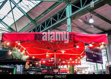 Borough Market 'Oliviers Bakery' stallholders branded red parasol with lit display bulbs inside the traditional Southwark Market Southwark London UK - Stock Image