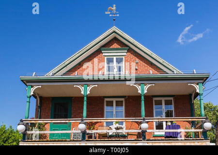 Second story balcony of an old 1900s red brick cottage style house with white and green trim plus decorated wooden posts - Stock Image