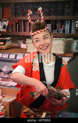 Japanese woman in traditional costume (a happi jacket) working at a seafood stall in a market. Old style Japan; - Stock Image
