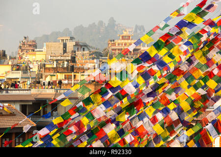 Colorful prayer flags at Boudanath Stupa with city houses in background, Kathmandu, Nepal - Stock Image