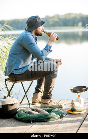 Handsome man relaxing with beer sitting alone during the fishing process on the pier near the lake - Stock Image