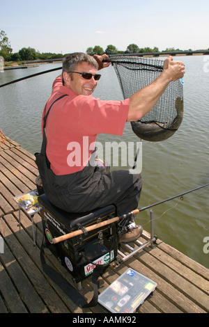 Man fishing for carp on lake near Daventry England - Stock Image