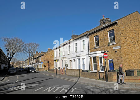 View of man walking and row of terraced housing on the corner of Dalyell Road and Pulross Rd in Brixton, South London England UK  KATHY DEWITT - Stock Image
