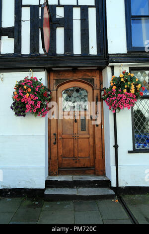 Wooden door surrounded by hanging basket of flowers on half timbered building in Market Street, Rye, East Sussex, UK - Stock Image