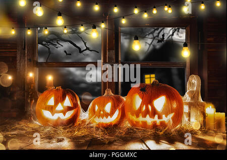 Scary halloween pumpkins on wooden planks, placed in front of window with scary background - Stock Image