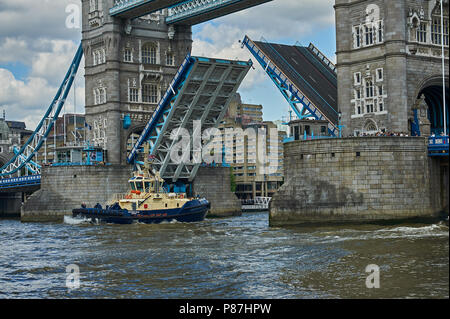 Tower Bridge across the River Thames in London opening to allow the passage of a tug boat. - Stock Image