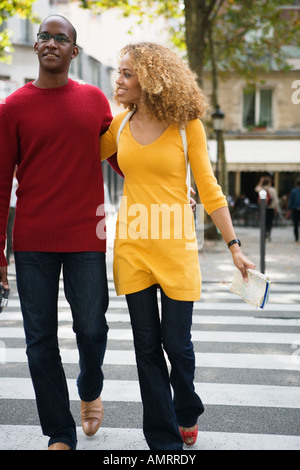 African couple walking across street - Stock Image