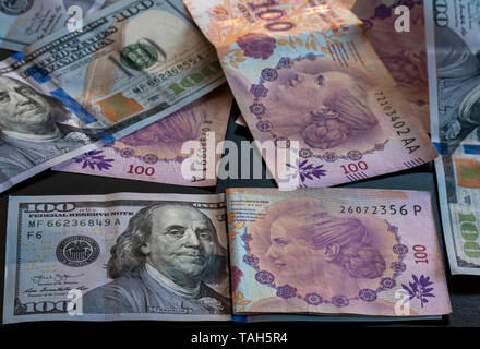 One hundred argentine pesos and one hundred dollars. - Stock Image