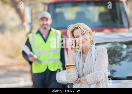Roadside mechanic behind woman on cell phone - Stock Image