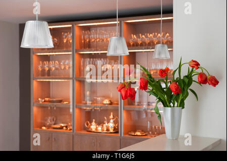 Vase of red flowers on counter by shelves of glassware - Stock Image