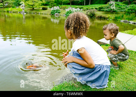 A young girl and boy sit by a pond at a public park - Stock Image