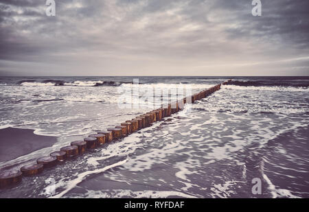 Wooden breakwater at sunrise, color toning applied. - Stock Image