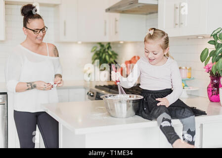 Mother and daughter baking in kitchen - Stock Image