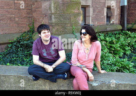 Woman and Young Man Seated on the Wall outside St. Paul's Episcopal Cathedral, Church Street, Downtown Buffalo, NY - Stock Image