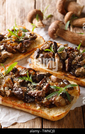 Open sandwiches with fried porcini mushrooms, caramelized onions, thyme and cheese close-up on the table. vertical - Stock Image
