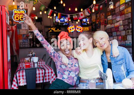 Portrait exuberant young women friends at bar - Stock Image