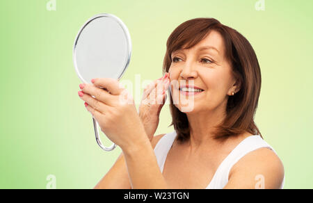 portrait of smiling senior woman with mirror - Stock Image