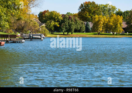 A small private lake or pond with boat or fishing docks in a neighborhood in Wichita, Kansas, USA. - Stock Image