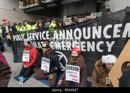 London, UK. 21st December 2018. Climate campaigners from Extinction Rebellion protest at the BBC with a banner 'Public Service Announcement - Climate Emergency'. They call onthe BBC to stop ignoring the climate emergency & mass extinctions taking place and promoting destructive high-carbon living through programmes such as Top Gear and those on fashion, travel, makeovers etc. The protest, organised by the Climate Media Coalition (CMC) and its director Donnachadh McCarthy brought mannequins wrapped in white cloth to the BBC representing the bodies of a Greek village killed by fire. Peter Marsha - Stock Image