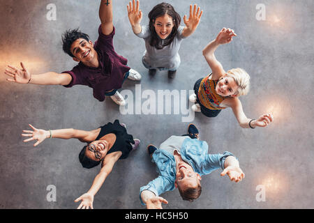 Top view of young students standing together looking up at camera with their hands raised in celebration. - Stock Image
