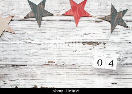 Fourth of July Background. Wooden stars and wood calendar blocks with the date July 4th to mark America's Independence Day. . - Stock Image
