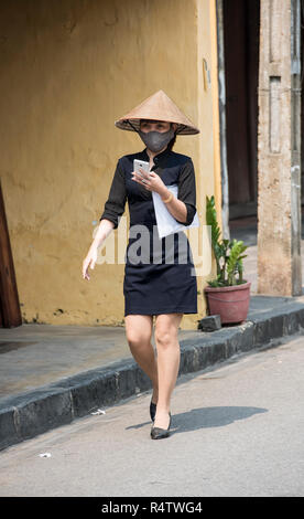Modern young Vietnamese lady using mobile phone whilst walking along traditional Hoi An street in Vietnam. - Stock Image