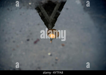 The light above a local bar is reflected in a puddle of water. - Stock Image