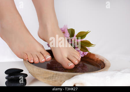 Female bare feet on wooden bowl with water in spa salon and decoration stones and flowers isolated on white background. Pedicure concept. Close up - Stock Image