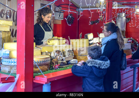 A pretty cheese seller at the Christmas market in Rennes, France waits on a mother and her son. - Stock Image