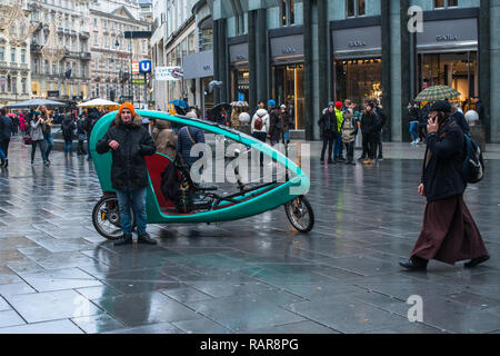 A bicycle taxi cab on Stephansplatz St Stephens Square on a rainy day, Vienna Austria Europe. - Stock Image