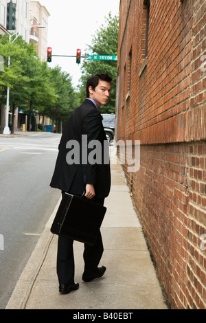 Asian business man walking down sidewalk in the city looking back at viewer - Stock Image