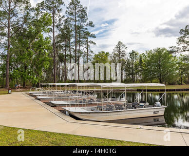 Okefenokee Swamp, Folkston, GA, USA-3/29/19: The canal at eastern entrance to the swamp, with skiffs at dock, and two women in background. - Stock Image