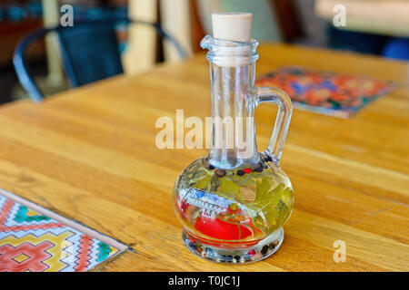 A glass bottle of fresh olive oil with whole pepper in corns and some herbs on a dinner table. Nobody around - Stock Image