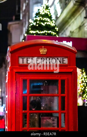 Iconic famous telephone box with Christmas decorate tree at the night in London - Stock Image