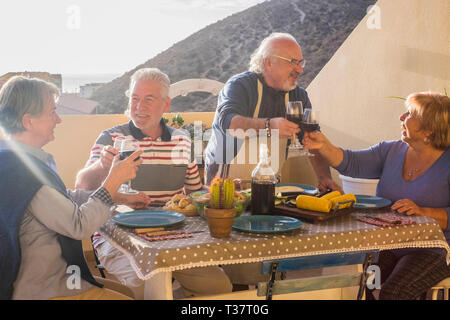 Happy cheerful group of senior aged old people enjoy together toasting and eating in friendship - retired people have fun having lunch in outdoor terr - Stock Image