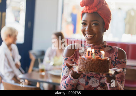 Portrait smiling, confident young woman holding birthday cake with candles - Stock Image