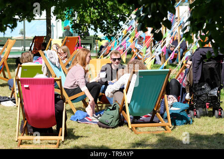 Hay Festival, Hay on Wye, Powys, Wales, UK - Friday 31st May 2019 - Visitors enjoy a break between events on the Festival lawns as the sun emerges on Friday afternoon. The eleven day Festival features over 800 events many aimed at children - the Hay Festival continues to Sunday 2nd June. Photo Steven May / Alamy Live News - Stock Image