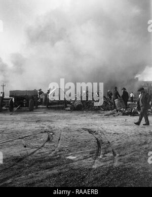 Men mill about a burning dump in Colorado, ca. 1925. - Stock Image