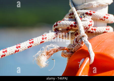 hanging orange life belt with long rope at the beach, security and safety concept - Stock Image
