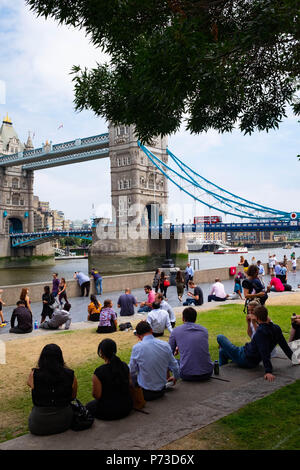 London, England. 4th July 2018. Tourists and office workers enjoy lunch time near London's Tower Bridge on another very hot day. The present heatwave is set to continue. ©Tim Ring/Alamy Live News - Stock Image