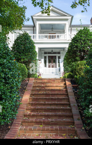 JONESBOROUGH, TN, USA-9/29/18: A set of brick steps leads up to an elegant white, two-story, 19th century home. - Stock Image