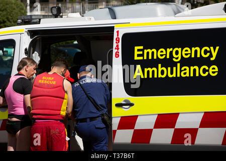 Surf rescue volunteer and paramedic attend to a near drowned man at Palm beach as he lies in the ambulance,Sydney,Australia - Stock Image